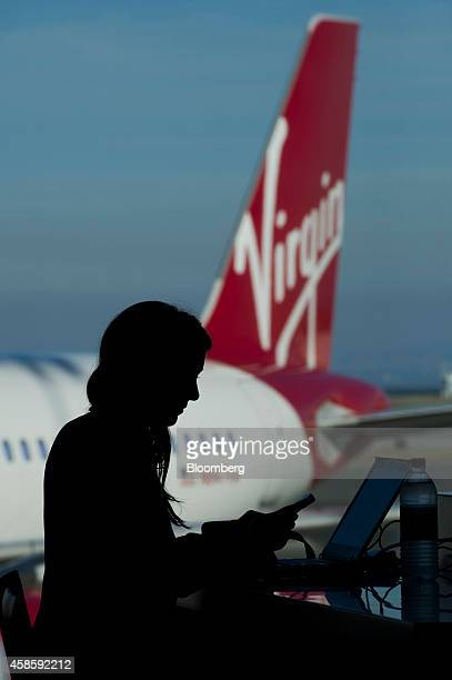 The silhouette of a traveler is seen using a mobile phone and laptop computer while waiting to board a Virgin America Inc Airbus A320 plane at San...