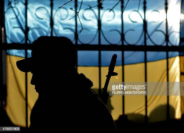 The silhouette of a Ukrainian soldier is seen against a Ukrainian flag as Ukrainian soldiers wait inside the Sevastopol tactical military brigade...