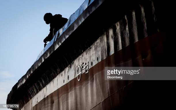 The silhouette of a worker is seen painting the Pacer tugboat as it undergoes repairs at the Seaspan Vancouver Shipyard in North Vancouver British...