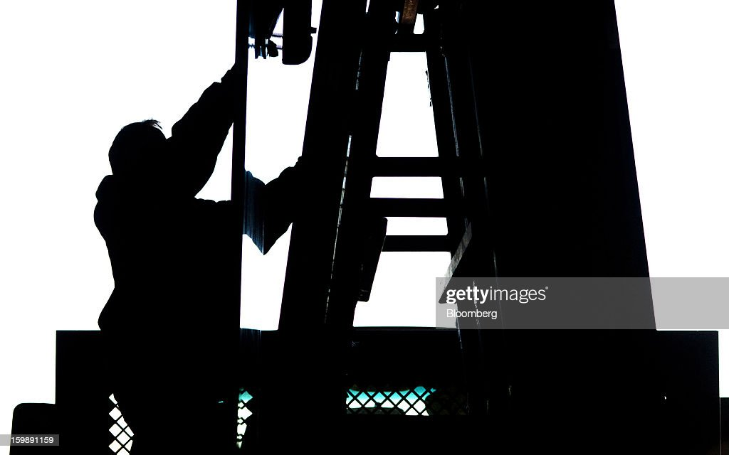 The silhouette of a worker using a crane to stack slabs of granite onto the back of a truck is seen at the Lang Stone Co. facility in Columbus, Ohio, U.S., on Friday, Jan. 18, 2013. The Lang Stone Co. drafting department serves architects, builders, masonry contractors and homeowners, by providing design options and producing scaled and fully-detailed drawings for fabrication and installation. Photographer Ty Wright/Bloomberg via Getty Images