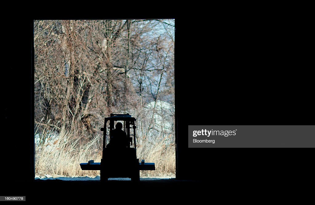 The silhouette of a worker using a forklift to move a slab of sandstone is seen at the Cleveland Quarries facility in Vermilion, Ohio, U.S., on Friday, Feb. 1, 2013. Spending on U.S. construction projects climbed more than forecast in December, showing the housing industry is sustaining gains that may lift the economy. Photographer: Ty Wright/Bloomberg via Getty Images