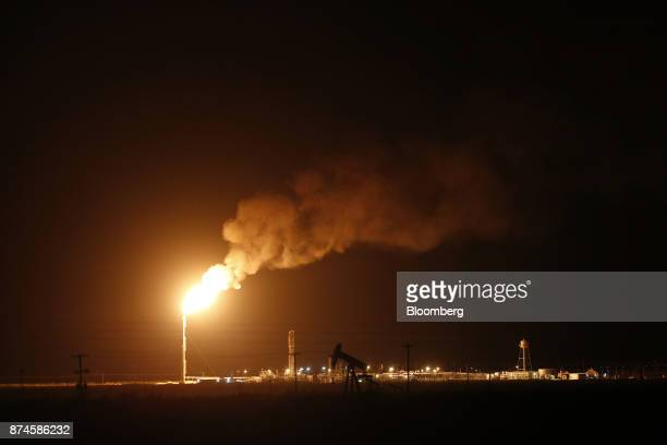 The silhouette of an electric oil pump jack is seen near a flare at night in the oil fields surrounding Midland Texas US on Tuesday Nov 7 2017...