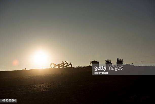 The silhouette of four pumpjacks are seen operating on the site of an oil well outside Williston North Dakota US on Thursday Feb 12 2015 A plunge in...