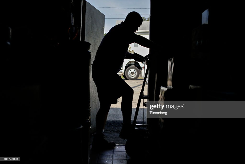 The silhouette of Josh McCartney, a driver with Baumgarten Distributing Co., is seen entering a cooler while delivering cases of SABMiller Plc Miller Lite brand beer in Chillicothe, Illinois, U.S., on Thursday, Sept. 17, 2015. Anheuser-Busch InBev NV unveiled plans to acquire SABMiller Plc yesterday, a deal that may cost the Budweiser brewer more than $100 billion as it seeks to unite the world's two biggest beermakers. Photographer: Daniel Acker/Bloomberg via Getty Images