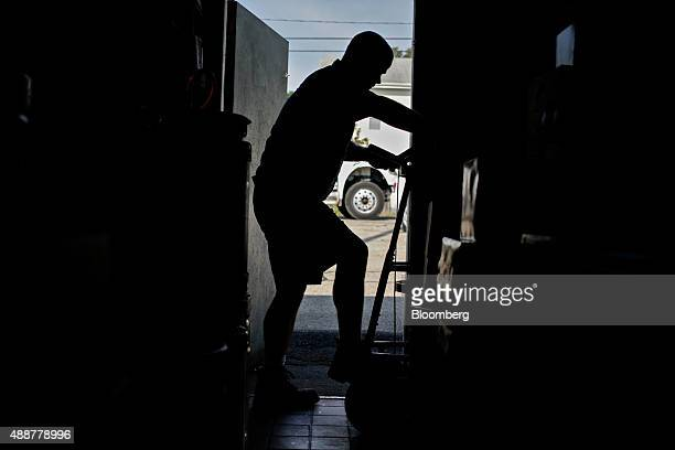 The silhouette of Josh McCartney a driver with Baumgarten Distributing Co is seen entering a cooler while delivering cases of SABMiller Plc Miller...