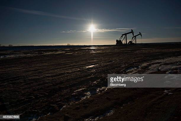 The silhouette of pumpjacks is seen on the site of an oil well outside Williston North Dakota US on Wednesday Feb 11 2015 A plunge in global energy...