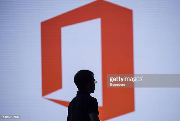 The silhouette of Qi Lu executive vice president of the applications and services group at Microsoft Corp is seen as he watches a presentation during...