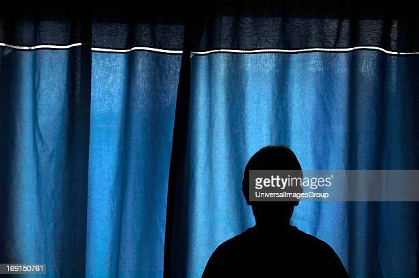 The Silhouetted Shape Of A 13yr Old BoyStanding In Front Of Blue Coloured Drawn Curtains