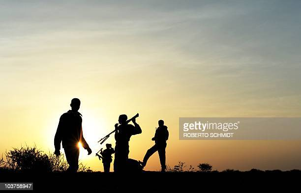 The silhouettes of armed men some pirates and some homegrown security forces appear on the horizon in the early morning in the semidesertic plains...