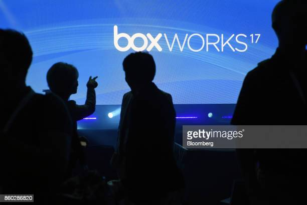 The silhouettes of attendees are seen waiting for the start of a keynote address during the BoxWorks 2017 Conference at the Moscone Center in San...