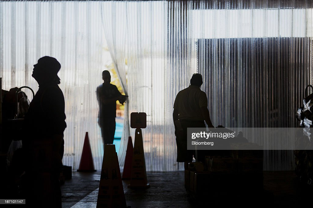 The silhouettes of employees are seen stocking the Specialty Produce warehouse in San Diego, California, U.S. on Friday, Nov. 1, 2013. The U.S. Bureau of Economic Analysis is scheduled to release gross domestic product (GDP) figures on Nov. 7. Photographer: Sam Hodgson/Bloomberg via Getty Images