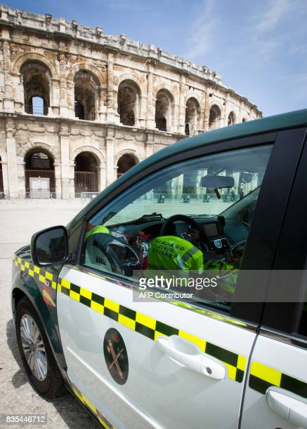 The silhouettes of members of the Spanish Civil Guard are reflected on the car's window during a patrol at the Arena in Nimes prior to the start of...