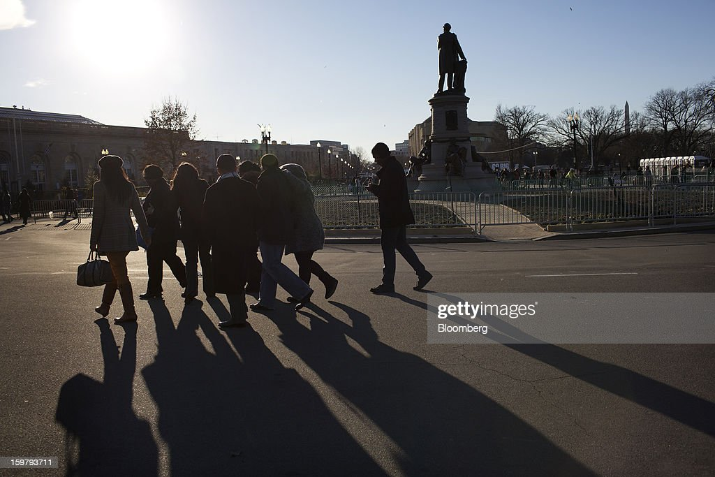 The silhouettes of pedestrians walking in front of the Capitol building are seen ahead of the presidential inauguration in Washington, D.C., U.S., on Sunday, Jan. 20, 2013. As he enters his second term U.S. President Barack Obama has shed the aura of a hopeful consensus builder determined to break partisan gridlock and adopted a more confrontational stance with Republicans. Photographer: Victor J. Blue/Bloomberg via Getty Images