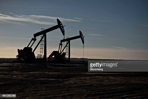 The silhouettes of pumpjacks are seen on the site of an oil well outside Williston North Dakota US on Wednesday Feb 11 2015 A plunge in global energy...