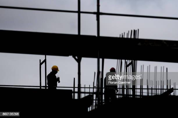 The silhouettes of two construction workers ic pictured on October 11 2017 in Berlin Germany