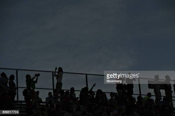 The silhouettes of viewers are seen during the solar eclipse totality on the campus of Southern Illinois University in Carbondale Illinois US on...