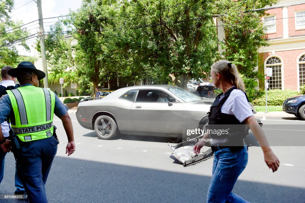 The silver Dodge Charger alledgedly driven by James Alex Fields Jr. passes by police officers near the Market Street Parking Garage moments after driving into a crowd of counter-protesters on Water Street on August 12, 2017 in Charlottesville, Virginia. Heather Heyer, 32 years old, was killed and 19 others injured when they were struck by Fields' car.