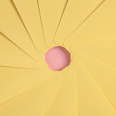 The simbol of an aperture of a camera is made from yellow paper on the pink background.