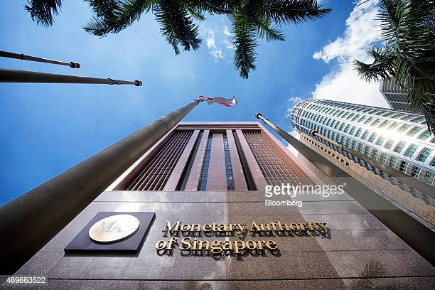 The Singapore national flag flies next to signage for the Monetary Authority of Singapore displayed outside the central bank's headquarters in...