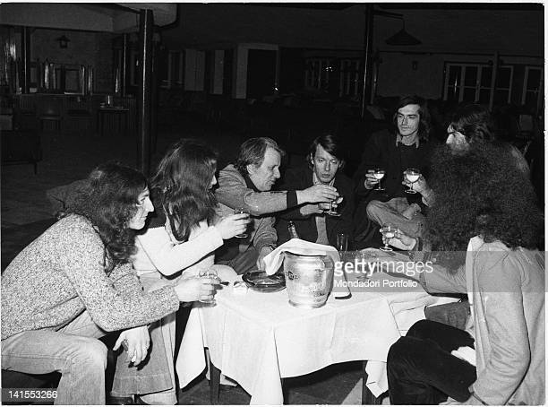 The singersongwriter Fabrizio De Andre drinking a toast with Sergio Bernardini the owner of the 'La Bussola' nightclub and the members of the band...