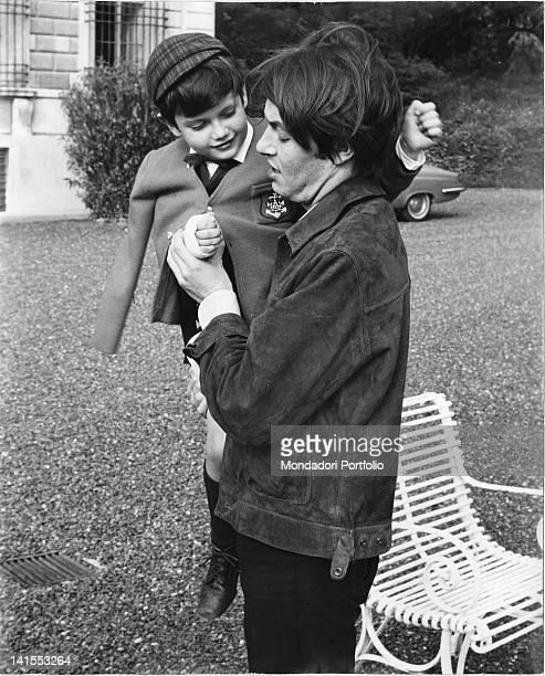 The singersongwriter Fabrizio De Andre holding son Cristiano on his lap in the garden of the family's villa Genoa 1968