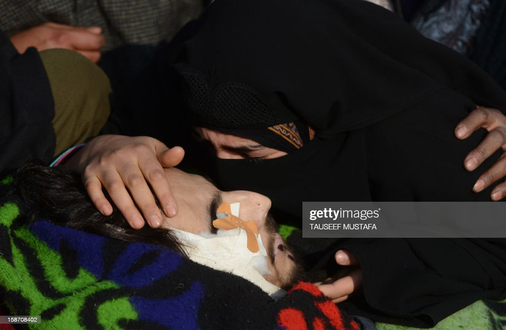The sister of alleged Pakistan-based Lashker-e-Toiba militant Mudasir Sheikh alias Mavia a self styled 'district commander' kisses his body during the funeral of he and his Pakistani associate Tamim in Kulgam district of south Kashmir some 75kms from Srinagar on December 25, 2012. Security forces confronted the pair of rebels and in the ensuing gunbattle they and a policeman were killed. A police spokesman said that the two were implicated in an attack on The Silver Star Hotel in Srinagar and on an army convoy. AFP PHOTO/Tauseef MUSTAFA