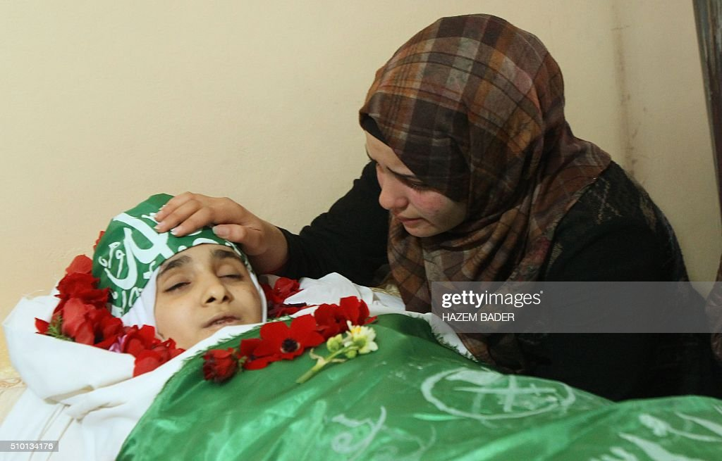 The sister of Palestinian Kalzar al-Uweiwi, a Palestinian teenager who was killed a day earlier following a reported stabbing attack, mourn over her body ahead of her funeral, in the Israeli occupied West Bank city of Hebron, February 14, 2016. Israeli forces shot dead Kalzar al-Uweiwi, 17, as she tried to stab a soldier in the city of Hebron on February 13, according to Israeli and Palestinian authorities. BADER