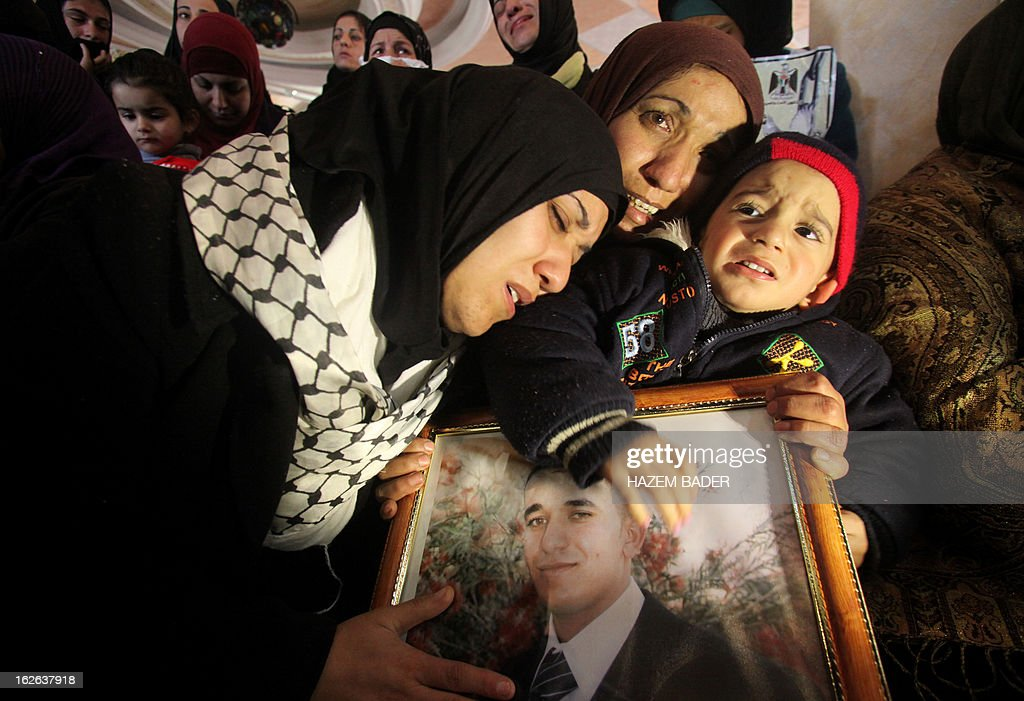 The sisters of Arafat Jaradat (picture), a Palestinian inmate who died in an Israeli prison, mourn their brother's death while embracing his son Muhannad (R) during his funeral in the West Bank village of Saair on February 25, 2013. Militants of the Al-Aqsa Martyrs Brigades, the armed wing of Palestinian president Mahmud Abbas' Fatah movement, vowed to avenge the death of Jaradat, a prisoner they say was tortured in an Israeli jail. AFP PHOTO/HAZEM BADER