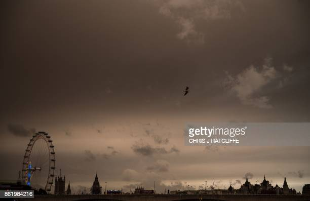 The sky darkens over the London Eye and the Houses of Parliament in London on October 16 2017 caused by warm air and dust swept up by storm Ophelia...
