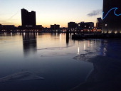 The skyline of Baltimore Maryland is reflected in a still and icy Inner Harbor on January 31 2014 AFP PHOTO/Michelle KWAJAFA