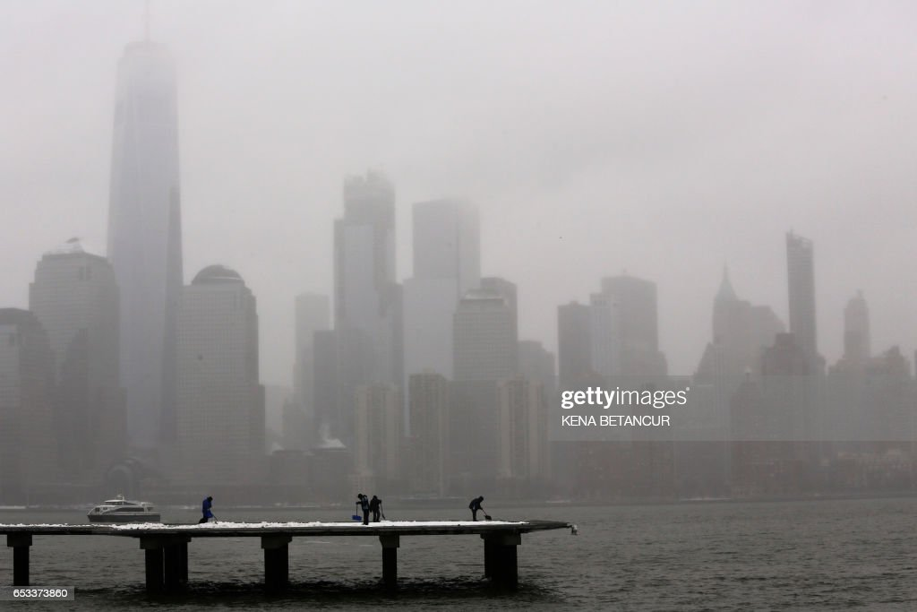TOPSHOT - The skyline of New York appears in the distance as people clean off snow on a dock March 14, 2017 in Jersey City, New Jersey. Winter Storm Stella dumped sleet and snow across the northeastern United States on Tuesday but spared New York from the worst after authorities cancelled thousands of flights and shut schools. Blizzard warnings were in effect in parts of Connecticut, Massachusetts and upstate New York, but were lifted for New York City, the US financial capital home to 8.4 million residents, where snow turned to sleet, hail and rain. BETANCUR
