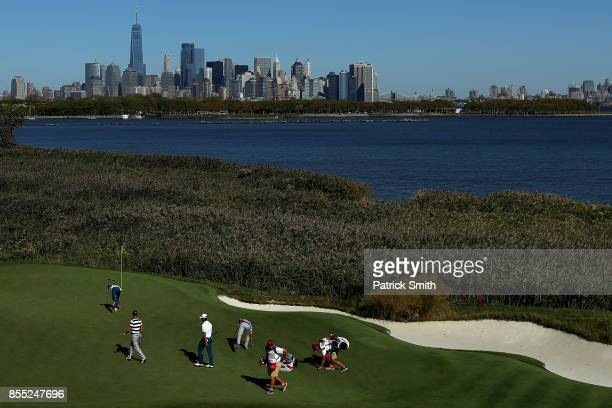 The skyline of New York City is seen as Rickie Fowler and Justin Thomas of the US Team walk on the tenth green with Hideki Matsuyama of Japan and the...