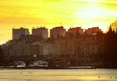 The skyline of Stockholm the capitol of Sweden 03 April 2004 seen at sunset from the island of Djurgarden with birds walking on the last ice as...