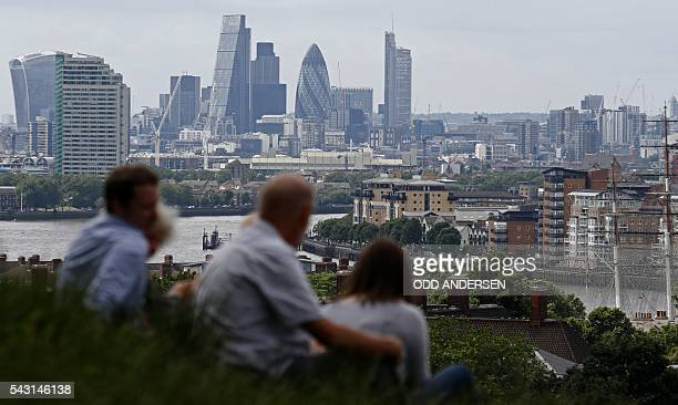 The skyline of the City of London is pictured on the horizon as people relax in Greenwich park in southeast London on June 26 2016 British business...