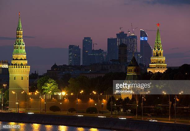 The skyscrapers of Moscow City business district center stand beyond the illuminated towers of Red Square and the Kremlin in Moscow Russia on...