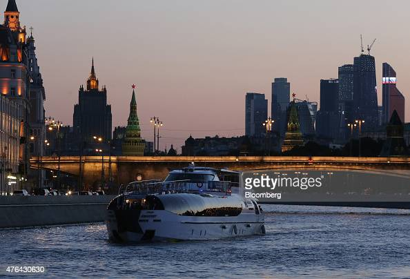 The skyscrapers of Moscow City business district right stand on the city skyline beyond an illuminated bridge and a city cruise on the Moscow river...