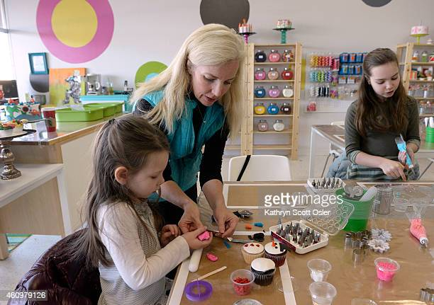 The Slavin family including mom Becca center and daughters Piper left and Dillen work on a variety of cupcakes at a table together Patrons at Make a...