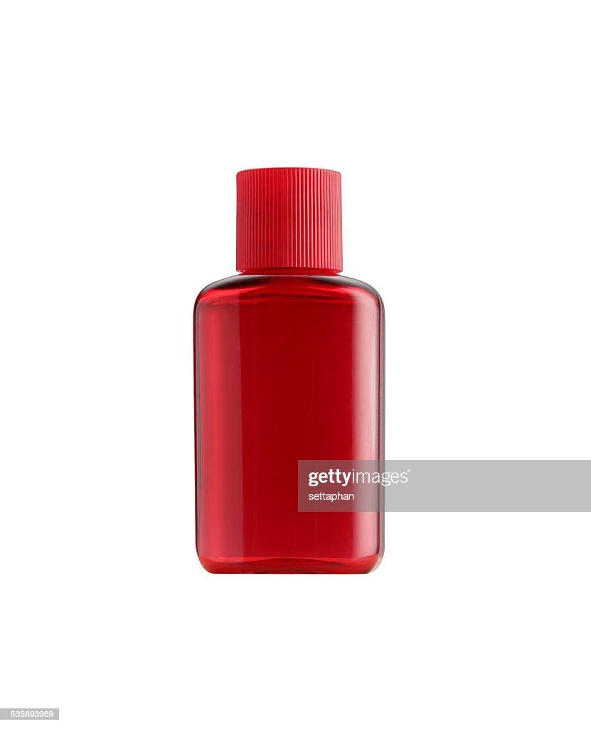 La piccola bottiglia colore rosso imballaggio isolato : Foto stock