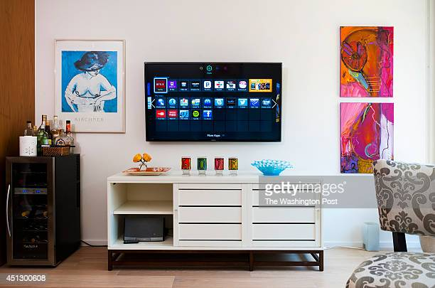 The Smart TV and a media consul along with a mini bar with a vintage art poster adorn the living room of Wendy Rieger's one bedroom condo April 24...