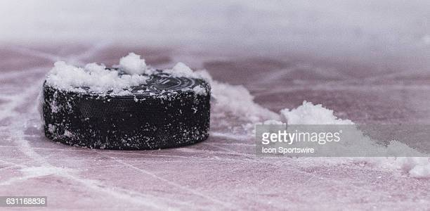 the snow covered puck sits on the ice in the faceoff dot during a stoppage in play between the Vancouver Canucks and Calgary Flames during a NHL...