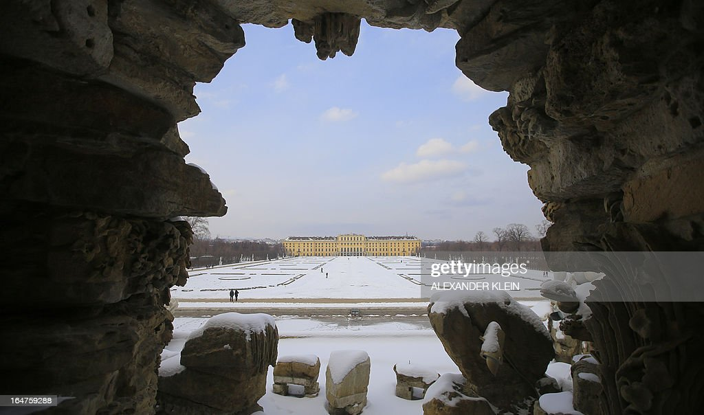 The snow-covered palace and gardens of Schoenbrunn are seen through fountain sculptures in Vienna on March 27, 2013. The Schoenbrunn Palace was the summer residence of the Habsburg family, one of the most important cultural monuments in Austria and part of the Unesco world cultural heritage sites.