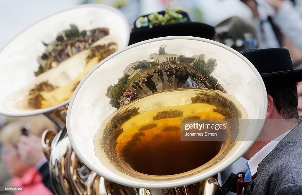 The so called 'Bavaria' giant bronze sculture and landmark of the Oktoberfest is reflected by the trumpets of brass musicians during the traditional 'Boellerschiessen' (firing of a salute with a special gun) on the last day of Oktoberfest beer festival on October 7, 2012 in Munich, Germany. The 'Boellerschiessen' officially signifies the closing of this year's edition of the world's biggest beer festival.
