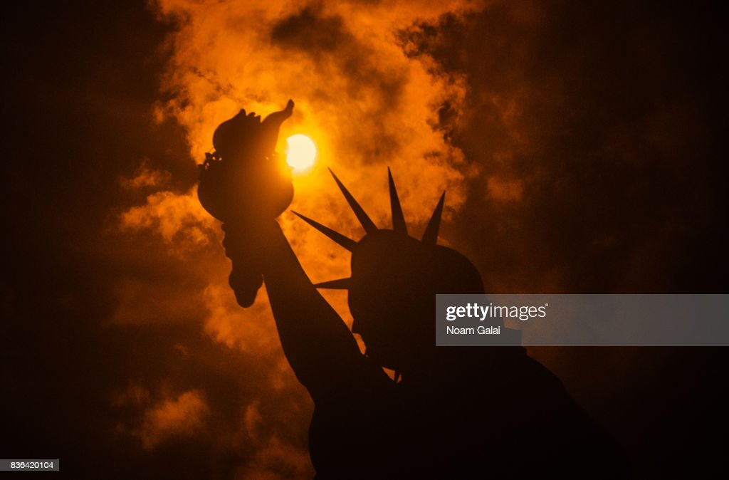 The solar eclipse is seen behind the Statue of Liberty at Liberty Island in on August 21, 2017 in New York City. While New York was not in the path of totality for the solar eclipse, around 72 percent of the sun was covered by the moon during the peak time of the partial eclipse.