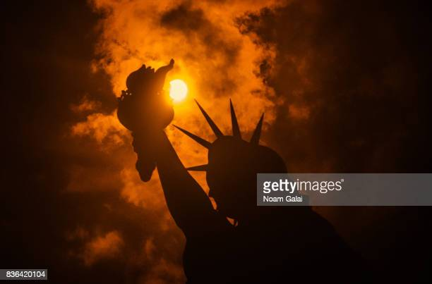 The solar eclipse is seen behind the Statue of Liberty at Liberty Island in on August 21 2017 in New York City While New York was not in the path of...