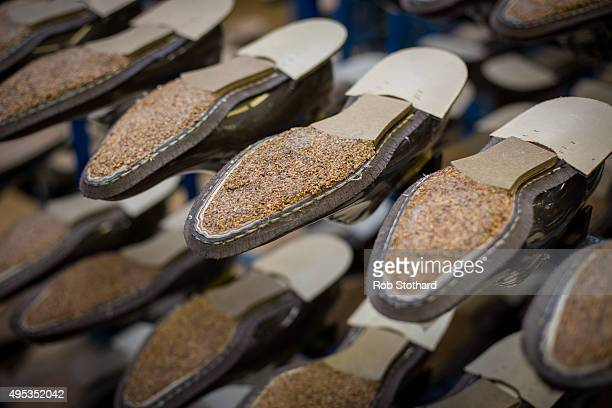 The soles of unfinished shoes are seen on racks inside the Joseph Cheaney and Sons factory on August 25 2015 in Desborough United Kingdom J Cheaney...