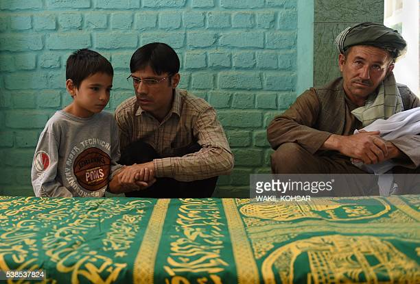 The son of Afghan reporter Zabihullah Tamanna Mustafa sits alongside his father's coffin ahead of his funeral prayers at a mosque in Kabul on June 7...