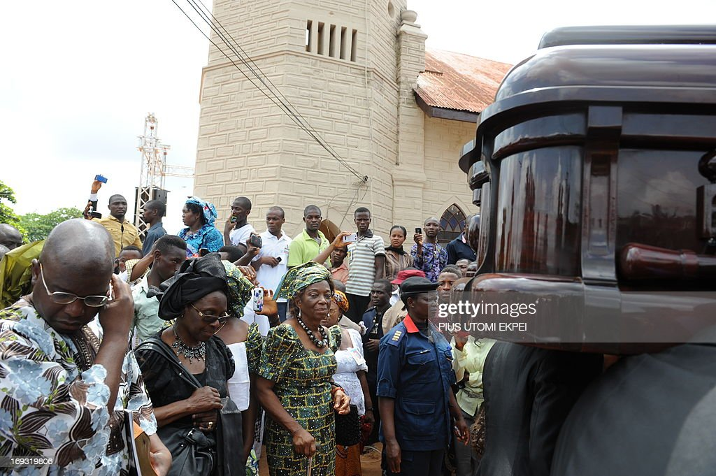 The son of author Professor Chinua Achebe, Dr. Ikechukwu Achebe (L), and his widow Professor Christie Achebe (2nd L) accompany the casket of late author during the funeral service at Ogidi in southeast Nigeria on May 23, 2013. Renowned author Professor Chinua Achebe was buried at his Ogidi country home. Hundreds of mourners gathered on Thursday in the hometown of Nigerian novelist Chinua Achebe for the funeral of the man regarded as the father of modern African literature and the author of the widely praised 'Things Fall Apart.'