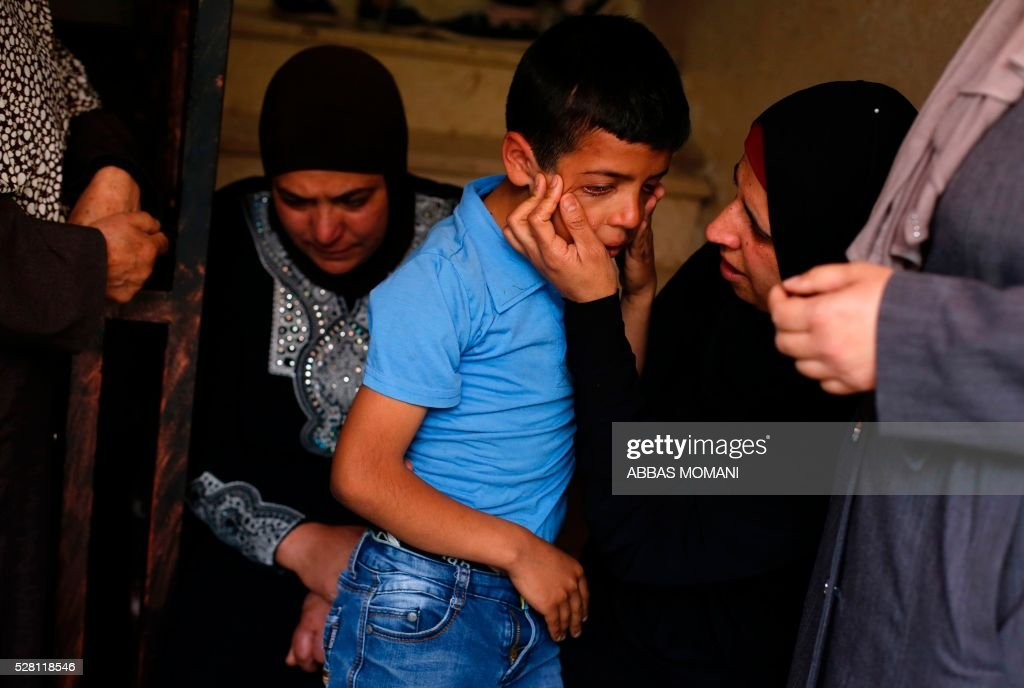 The son (C) of Palestinian Ahmed Shahaada, 36, who was shot dead by Israeli troops after ramming his vehicle into three Israeli soldiers in the occupied West Bank, mourns during his father's funeral in Betunia, near the city of Ramallah, on May 4, 2016. A Palestinian rammed his car into a group of Israeli soldiers in the occupied West Bank on May 3, injuring three before being shot dead, the Israeli army said. The army later confirmed that the injured were soldiers, and said they were taken to hospital for treatment without giving further details. MOMANI