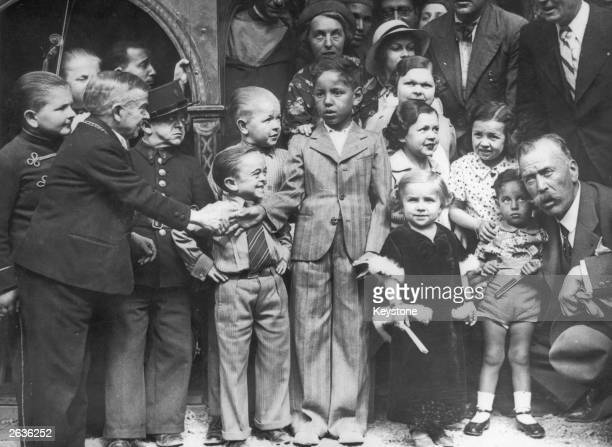 The son of the Sultan of Morocco shaking hands with a Major in a crowd of midgets at the Paris exhibition