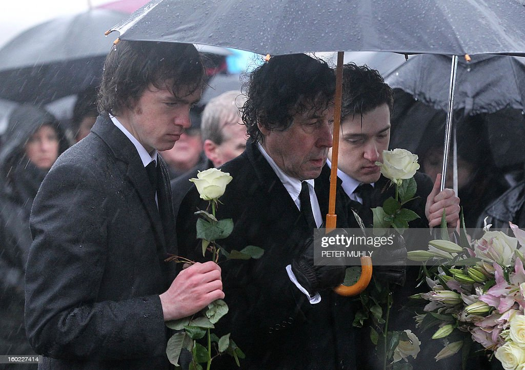 The sons of convicted Old Bailey bomber Dolours Price, Danny (L) and Oscar (R), stand with her ex-husband Stephen Rea (C), at Milltown cemetary in Belfast, Northern Ireland, on January 28, 2013. Price, convicted for the infamous IRA bombing of the Old Bailey court in London in 1973, was found dead at her home in Ireland, her family said January 24, 2013. Price was one of a number of high-profile IRA members who gave accounts of their past to Boston College in a series of interviews as part of the US university's oral history of the Northern Ireland conflict. AFP PHOTO / PETER MUHLY